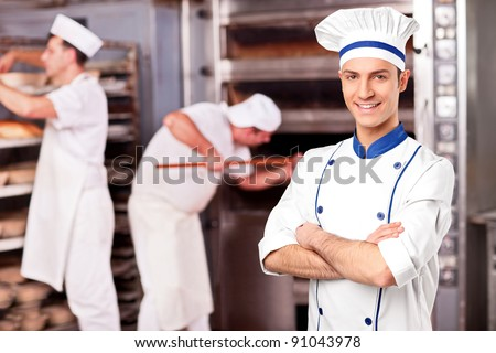 Portrait of a chef standing inside a bakery - stock photo