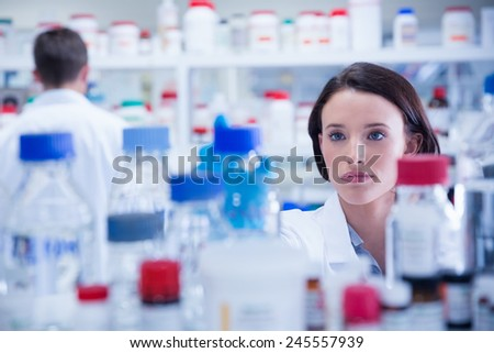 Portrait of a chemist behind medical sample in lab - stock photo
