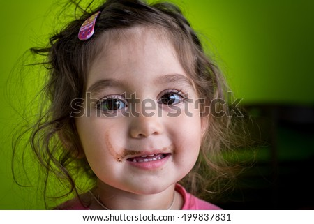 Portrait of a child - a girl. She smiles. Her face was smeared with a strip of chocolate.