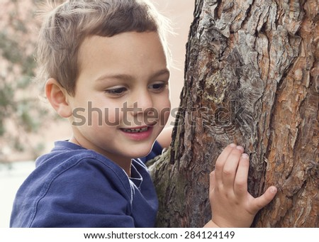 Portrait of a child boy holding and hugging tree trunk.