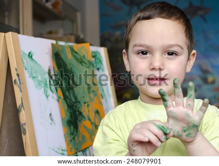 Portrait of a child boy  painting a colorful abstract picture with a brush and poster paint colors.