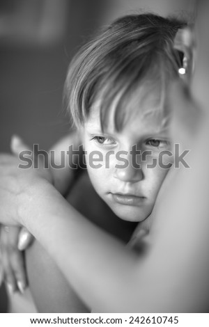 Portrait of a child cuddling with his parent, monochrome - stock photo