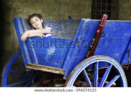 Portrait of a child girl in a blue wooden cart - stock photo