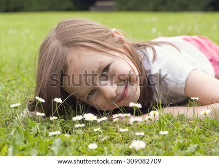 Portrait of a child girl lying on grass in garden or meadow with daisy flowers - stock photo