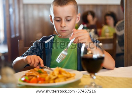 Portrait of a child having lunch in a restaurant - stock photo