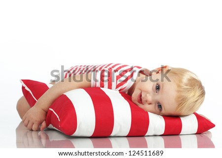 Portrait of a child lying on soft pillow studio shot - stock photo