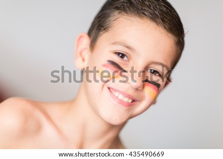 Portrait of a child with the flag of Germany painted on his face - stock photo