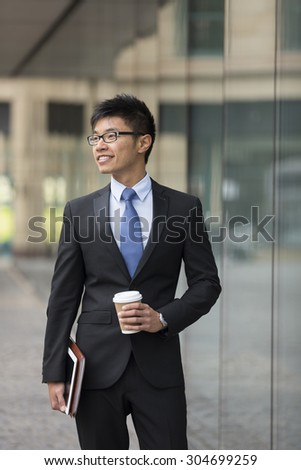 Portrait of a Chinese businessman outside modern office building, looking away.
