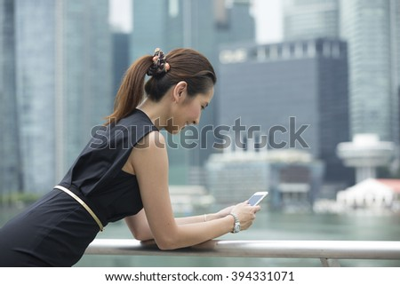Portrait of a Chinese businesswoman standing outside using her smart phone to send a message. - stock photo