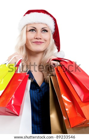 Portrait of a Christmas woman in santa hat holding a shopping bags over white background - stock photo