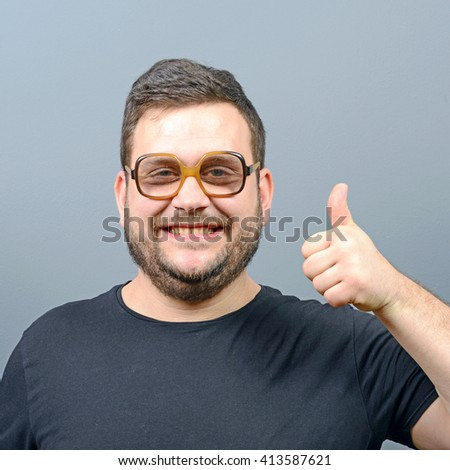 Portrait of a chubby geek showing thumbs up against gray background - stock photo