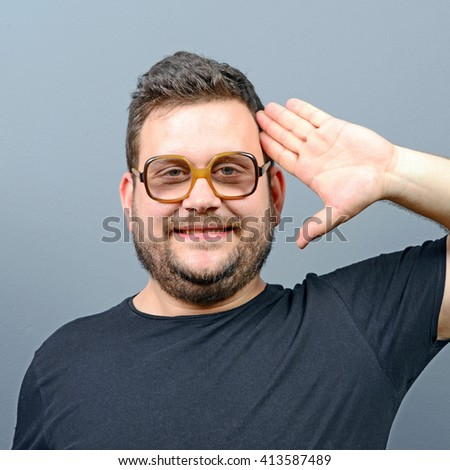 Portrait of a chubby man saluting against gray background