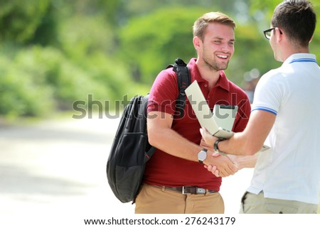 portrait of a college student with backpack happy to meet his friend and then shake hands with copy space - stock photo
