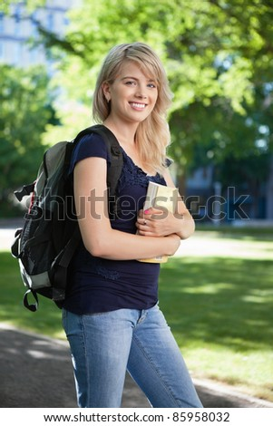 Portrait of a college student with book and bag - stock photo