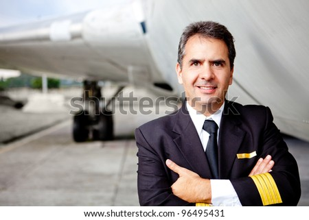 Portrait of a commercial airplane pilot smiling - stock photo