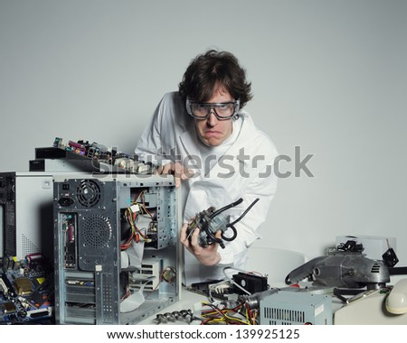 Portrait of a Computer technician with a computer destroyed - stock photo