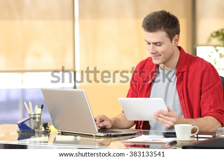 Portrait of a concentrated entrepreneur working on line with technology equipment sitting in a desktop at office - stock photo
