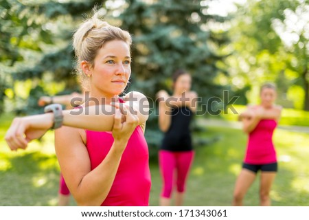 Portrait of a concentrated young woman streching her arm before jogging with friends - stock photo