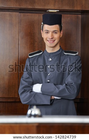 Portrait of a concierge in hotel with his arms crossed - stock photo