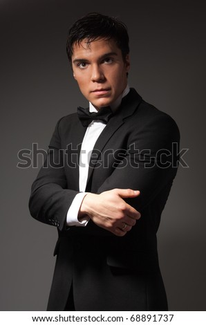 Portrait of a confident adult and mature businessman on dark background - stock photo