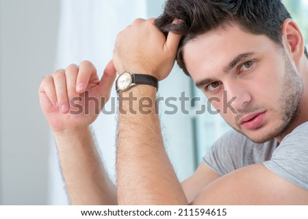 Portrait of a confident and handsome man. Young man sitting and holding a hand to his head and looks straight into the camera. Handsome man wearing a T-shirt - stock photo