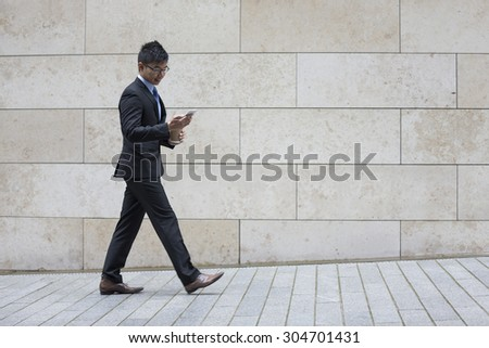 Portrait of a confident asian businessman walking in the city. - stock photo