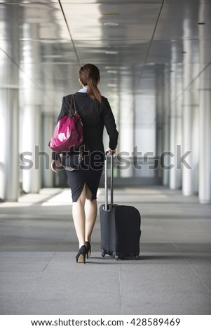 Portrait of a confident asian businesswoman walking in the city. - stock photo