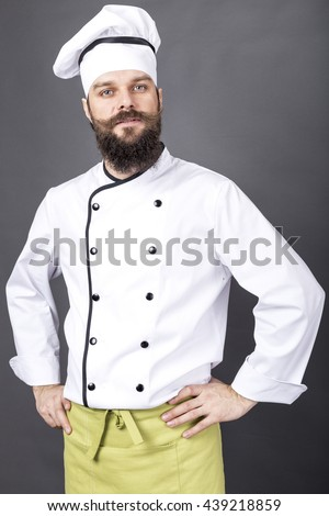 Portrait of a confident bearded chef over gray background - stock photo