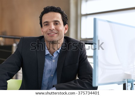 Portrait of a confident businessman at work in his glass office - stock photo