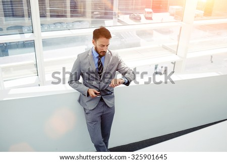 Portrait of a confident businessman dressed in luxury corporate clothing checking time on his watches and holding digital tablet, young successful managing director using touch pad during work break  - stock photo