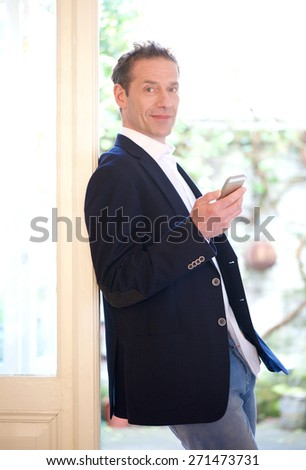 Portrait of a confident businessman holding mobile phone