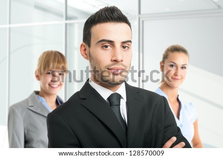 Portrait of a confident businessman in front of his team - stock photo