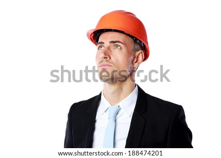 Portrait of a confident businessman in helmet looking up over white background - stock photo