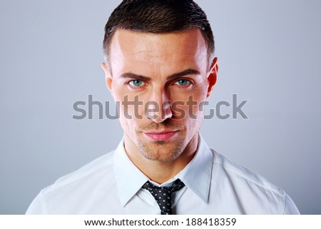 Portrait of a confident businessman over gray background - stock photo