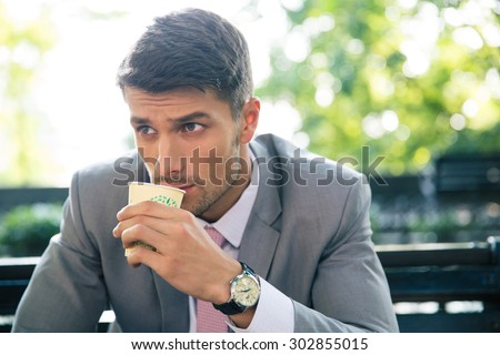 Portrait of a confident businessman sitting on the bench and drinking coffee outdoors - stock photo