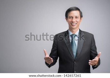 Portrait of a confident businessman standing against a grey background - stock photo