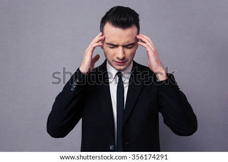 Portrait of a confident businessman thinking over gray background - stock photo