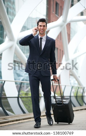 Portrait of a confident businessman traveling with phone and bag - stock photo