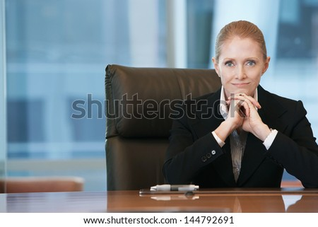 Portrait of a confident businesswoman sitting at conference table - stock photo