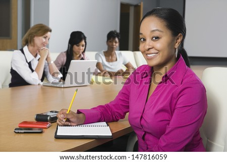 Portrait of a confident businesswoman with multiethnic colleagues in conference room - stock photo
