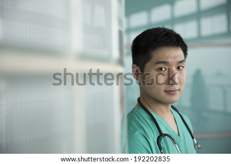 Portrait of a confident Chinese surgeon or doctor wearing green scrubs. Medical people portrait. - stock photo