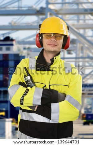 Portrait of a confident docker, wearing all required personal protective equipment, posing in front of an industrial container terminal and harbor - stock photo