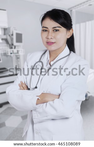 Portrait of a confident doctor wearing coat and arms crossed while standing in clinic