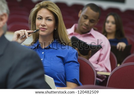 Portrait of a confident female executive in business lecture amid colleagues