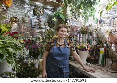 Portrait of a confident female florist in shop - stock photo