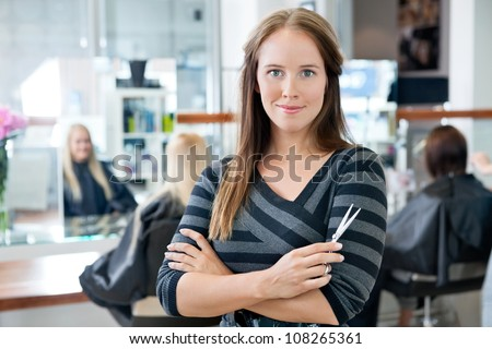 Portrait of a confident female hairdresser standing hands folded with people in background - stock photo