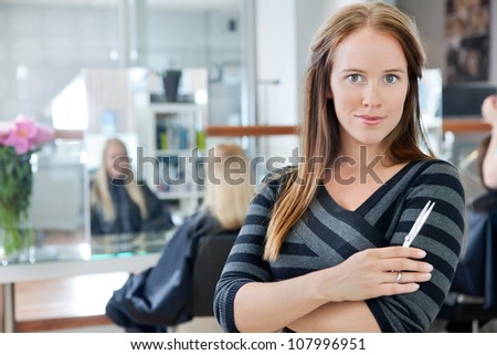 Portrait of a confident female owner of parlor standing arms crossed with people in background