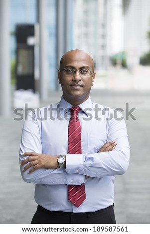 Portrait of a confident Indian Business man standing in modern city. Business man looking at camera. - stock photo
