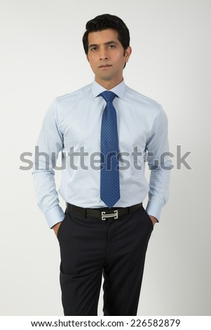 portrait of a confident Indian businessman isolated on grey - stock photo