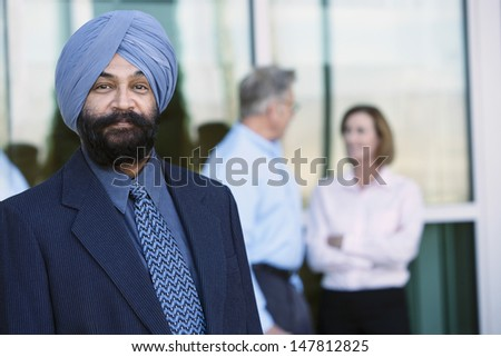 Portrait of a confident Indian businessman with colleagues in the background - stock photo